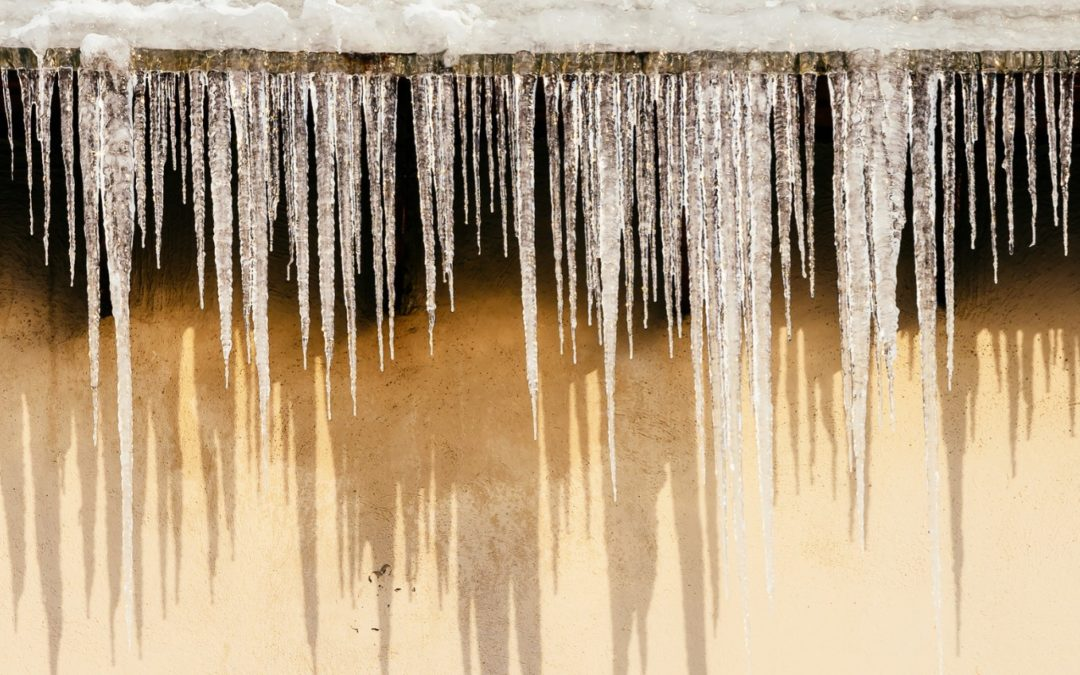 Icicles hanging from residential roof line.